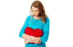 Mujer joven con la almohada en forma de corazón Fotos de archivo