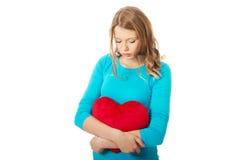 Mujer joven con la almohada en forma de corazón Imagen de archivo