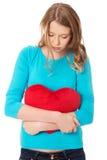 Mujer joven con la almohada en forma de corazón Imagenes de archivo