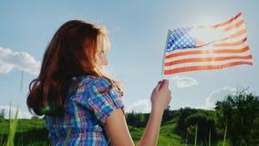 Mujer joven con la bandera americana en el sol metrajes