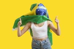 Mujer joven con la bandera brasileña en cara que gesticula los pulgares para arriba sobre fondo amarillo Fotos de archivo libres de regalías