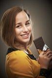 Mujer joven con la barra de chocolate Imagenes de archivo