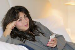 Mujer joven con la bata usando su teléfono en la cama Imágenes de archivo libres de regalías