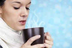 Mujer joven con la bebida caliente Foto de archivo libre de regalías