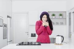 Mujer joven con la bebida caliente en cocina Fotos de archivo libres de regalías