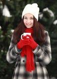 Mujer joven con la bebida caliente en el invierno al aire libre Imagen de archivo