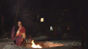 Mujer joven con la bebida caliente por el fuego almacen de metraje de vídeo