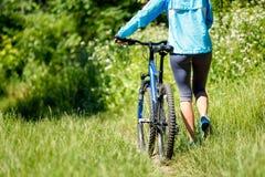 Mujer joven con la bici de montaña Foto de archivo libre de regalías