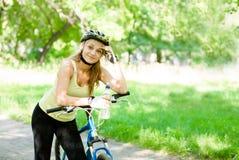 Mujer joven con la bici de montaña y la botella de agua a disposición Imagenes de archivo