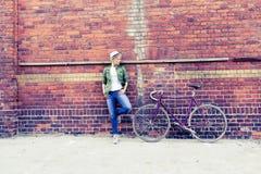 Mujer joven con la bici del camino del vintage en ciudad Foto de archivo