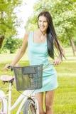 Mujer joven con la bicicleta Imagenes de archivo