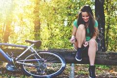 Mujer joven con la bicicleta Fotos de archivo