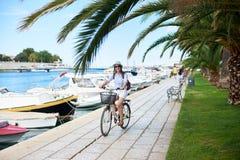 Mujer joven con la bicicleta de la ciudad del montar a caballo de la mochila cerca del mar imagenes de archivo