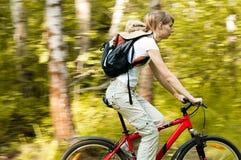 Mujer joven con la bicicleta en bosque Imagen de archivo libre de regalías