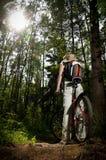 Mujer joven con la bicicleta en bosque Fotografía de archivo