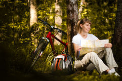 Mujer joven con la bicicleta en bosque Foto de archivo libre de regalías