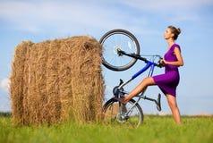 Mujer joven con la bicicleta en el campo Imagen de archivo