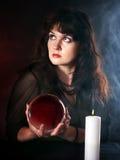 Mujer joven con la bola de cristal. Fotos de archivo