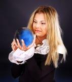 Mujer joven con la bola de cristal. Imagen de archivo libre de regalías