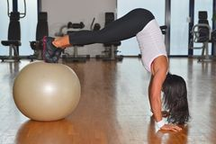 Mujer joven con la bola del gimnasio en el gimnasio Fotografía de archivo libre de regalías