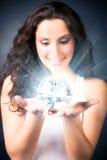 Mujer joven con la bola mágica del brillo Fotos de archivo