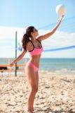 Mujer joven con la bola que juega a voleibol en la playa Fotos de archivo