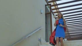Mujer joven con la bolsa de golf abajo de las escaleras metrajes