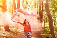 Mujer joven con la bomba de humo rosada del color imagenes de archivo