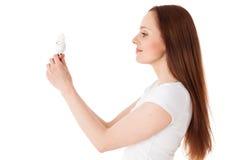 Mujer joven con la bombilla económica de energía Imagen de archivo libre de regalías