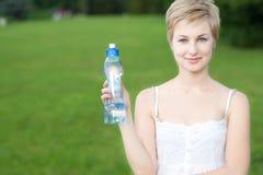 Mujer joven con la botella de agua al aire libre Foto de archivo