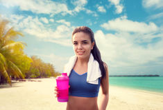 Mujer joven con la botella del deporte en la playa foto de archivo