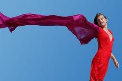Mujer joven con la bufanda que agita roja en el cielo azul Foto de archivo