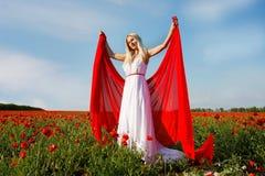 Mujer joven con la bufanda roja en campo de la amapola Fotos de archivo libres de regalías