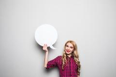 Mujer joven con la burbuja del discurso en fondo gris Imagen de archivo libre de regalías