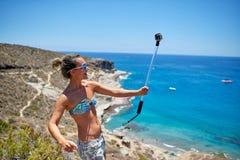 Mujer joven con la cámara de la acción en costa mediterránea Fotos de archivo libres de regalías