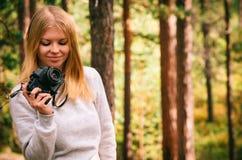 Mujer joven con la cámara retra de la foto al aire libre Fotografía de archivo libre de regalías