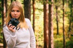 Mujer joven con la cámara retra de la foto al aire libre Fotos de archivo libres de regalías