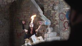 Mujer joven con la cara blanca que sopla hacia fuera el fuego en el edificio abandonado delante de la pared El concepto de la dem almacen de metraje de vídeo