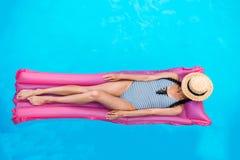 Mujer joven con la cara de la cubierta del sombrero de paja que flota en el colchón de aire fotografía de archivo