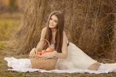 Mujer joven con la cesta del aplle al aire libre Imagen de archivo