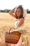 Mujer joven con la cesta llena de oídos trigo y sombrero Imagenes de archivo
