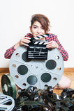 Mujer joven con la chapaleta de la película detrás del carrete grande del cine Imagen de archivo