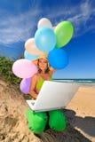 Mujer joven con la computadora portátil en la playa Foto de archivo