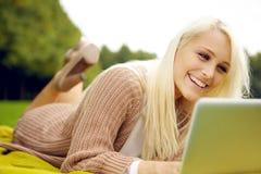Mujer joven con la computadora portátil en parque Imagenes de archivo