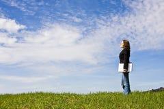 Mujer joven con la computadora portátil en prado imagen de archivo libre de regalías