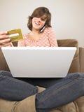 Mujer joven con la computadora portátil, haciendo compras vía el teléfono Imagenes de archivo
