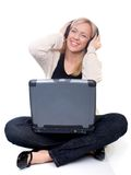 Mujer joven con la computadora portátil que escucha la música Fotos de archivo