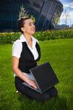 Mujer joven con la computadora portátil que se sienta en césped Fotografía de archivo libre de regalías