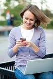 Mujer joven con la computadora portátil y el teléfono celular Foto de archivo