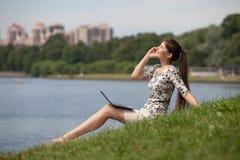 Mujer joven con la computadora portátil y el teléfono móvil en parque. fotos de archivo